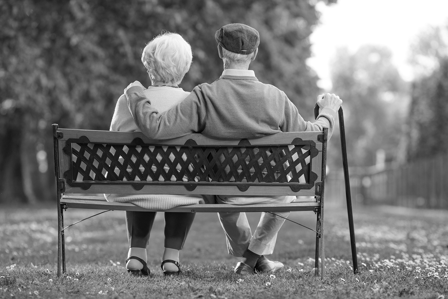 Elderly couple sitting on a couch in a park
